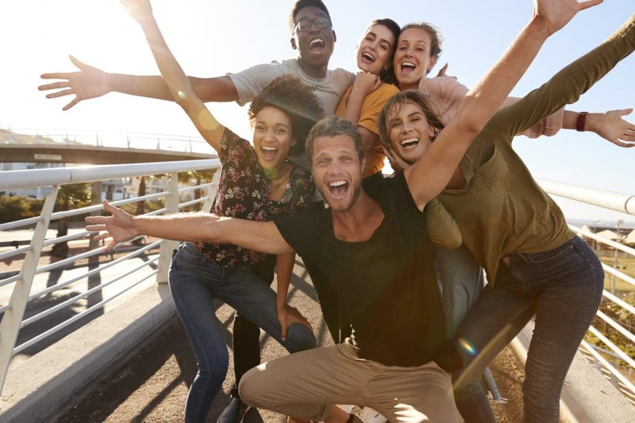 Photograph of a group of friends with their arms thrown open smiling and laughing outdoors.