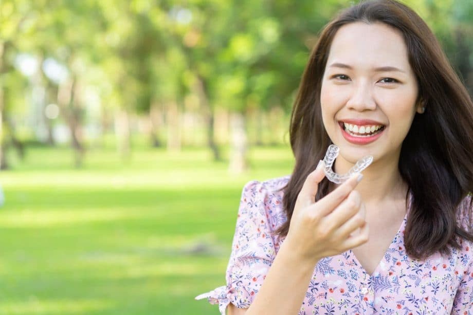 Woman with straight brown hair holding a pair of Invisalign aligners while sitting in a park on a sunny day.