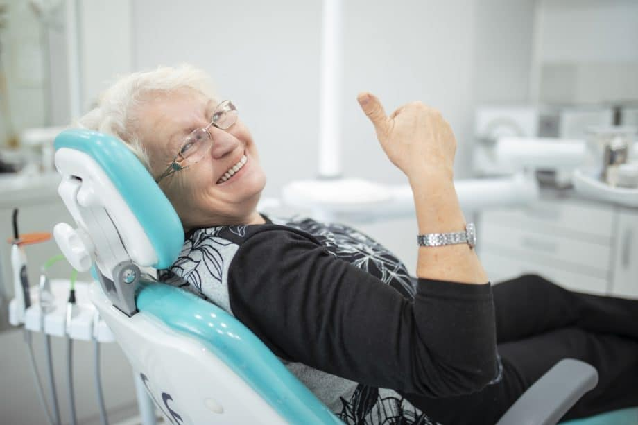 Photograph of an older woman with short white hair sitting in a dentists chair smiling and giving a thumbs-up.